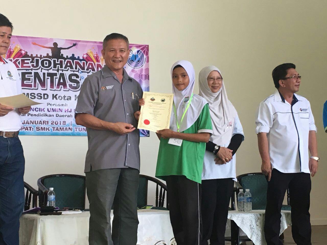 Nur Katija Seurus menerima sijil daripada Pegawai Pendidikan Daerah Kota Kinabalu, Umin bin Hj. Sadi